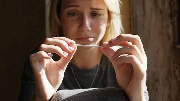 Close-up van huilende jonge vrouw zittend op de vensterbank en bedroefd over het positieve resultaat van de zwangerschapstest