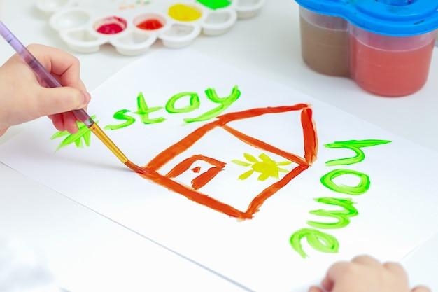 Close-up van huis geschilderd op een wit vel papier met de woorden stay home.