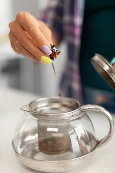 Close up van huisvrouw die groene thee brouwt tijdens het ontbijt in de keuken
