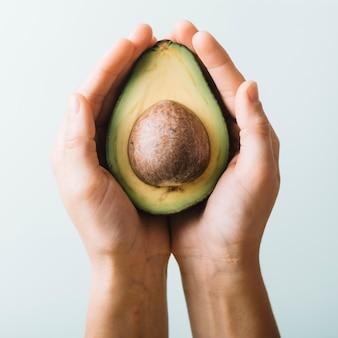 Close-up van iemands hand met avocado
