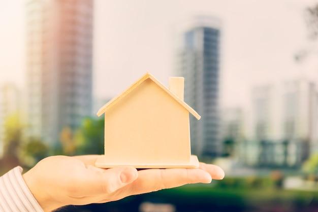 Close-up van iemands hand met houten huis model tegen de skyline van de stad
