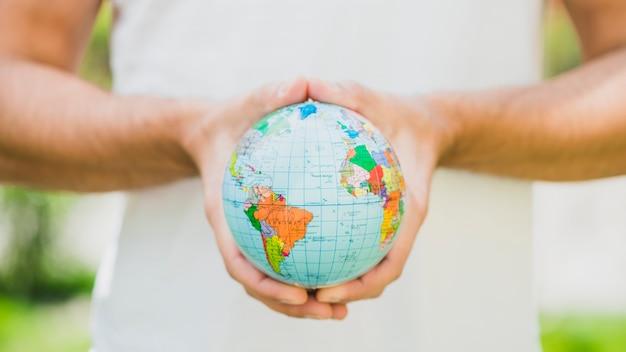Close-up van iemands hand met kleine wereld