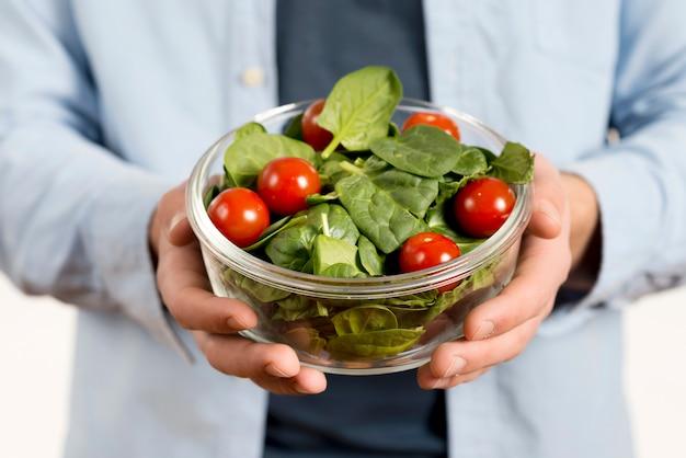 Close-up van iemands hand met kom salade