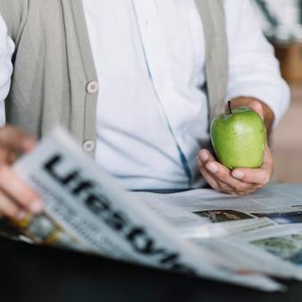 Close-up van iemands hand met krant en groene appel