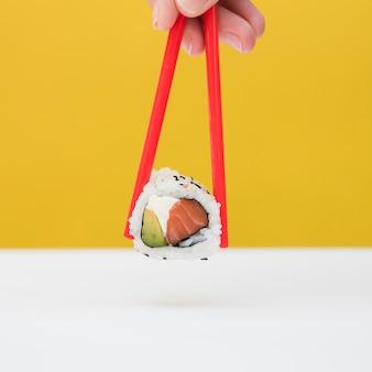 Close-up van iemands hand met sushi met rode stokjes tegen gele achtergrond