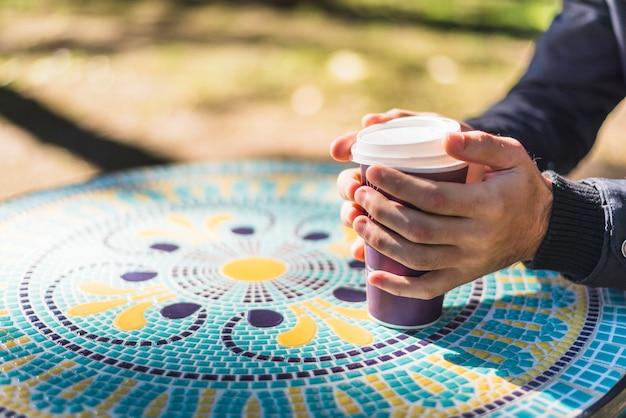 Close-up van iemands hand met wegwerp koffiekopje
