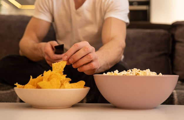 Close up van iemands hand nemen chips uit kom op tafel. wazig zicht op een man die de afstandsbediening vasthoudt en tv of film kijkt. kommen met chips en popcorn op tafel. concept van thuis rusten