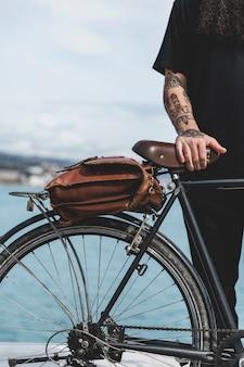 Close-up van iemands hand op fiets met bruine tas