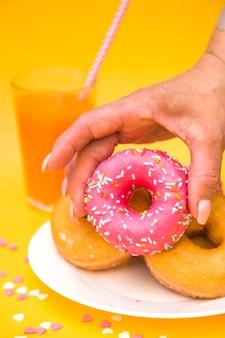 Close-up van iemands hand oppakken van roze donut van plaat