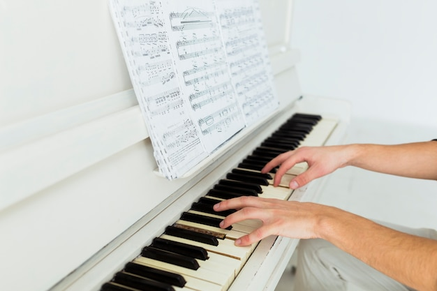 Close-up van iemands hand piano spelen