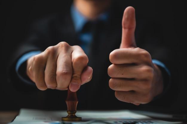 Close-up van iemands hand stempelen met goedgekeurde stempel op document aan bureau