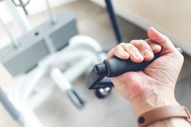 Close-up van iemands hand trek kabel gewicht in een fitnessruimte.