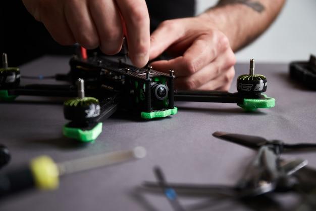 Close-up van iemands handen die een drone uit onderdelen assembleren, met behulp van gereedschap, snelle race-quadcopter voorbereiden op de vlucht. repareer de drone vóór het trainingsproces.