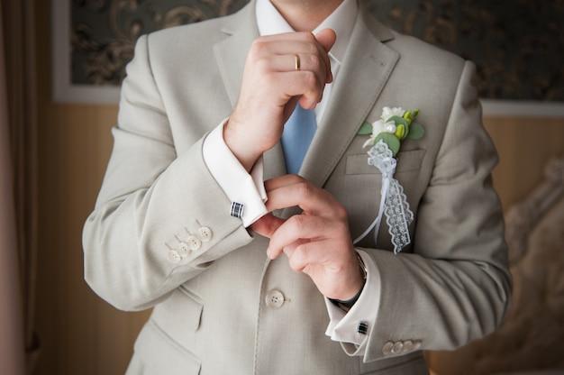 Close-up van iemands handen met ring, stropdas en manchetknoop.