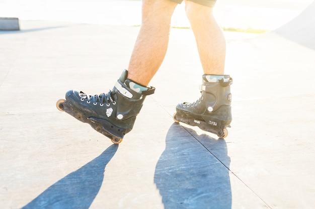 Close-up van iemands voeten rolschaatsen in skatepark