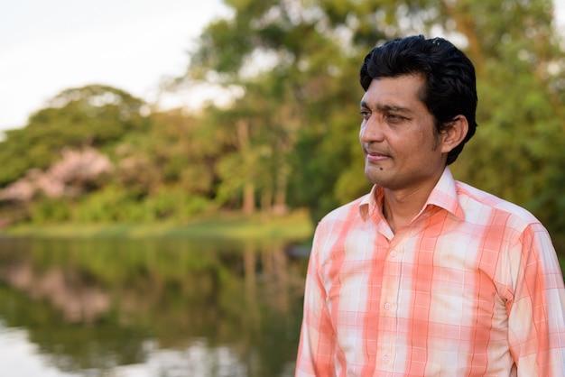 Close up van indiase man denken tegen schilderachtig uitzicht op het meer