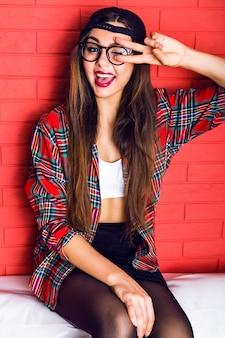 Close-up van indoor portret van jonge mooie hipster meisje met lange brunette haren en lichte make-up, yo wetenschap tonen en lachen,