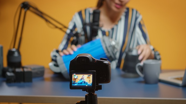 Close up van influencer-opname op camera videolicht review. social media-ster die online interessante inhoud maakt over professionele videoapparatuur voor webabonnees en distributie