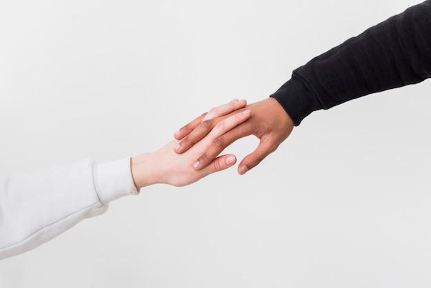 Close-up van interracial paar die elkaars handen houden tegen witte achtergrond