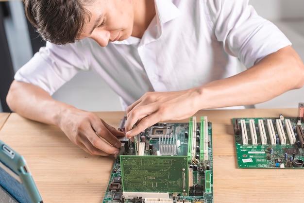 Close-up van it mannelijke technicus die het computer mainboard herstelt