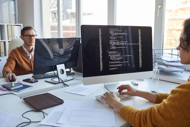 Close-up van it-ontwikkelaar die code op computerscherm schrijft terwijl hij samenwerkt aan een project met een team van softwareontwerpers, kopieer ruimte
