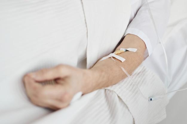 Close up van iv infuusbuizen en katheter in de hand van onherkenbare senior man, kopieer ruimte