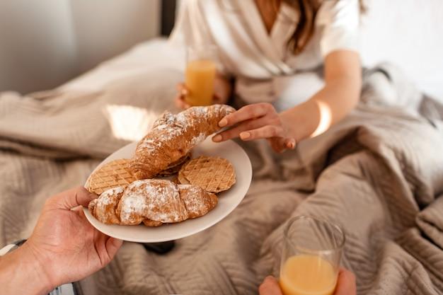 Close-up van jong koppel met heerlijk ontbijt op bed. romantische ochtend met verse croissants, koekjes en sap