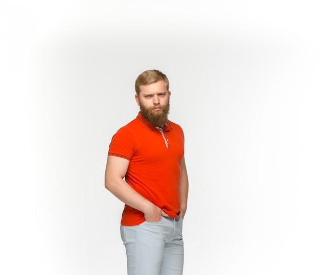 Close-up van jong man lichaam in lege rode t-shirt die op witte achtergrond wordt geïsoleerd.