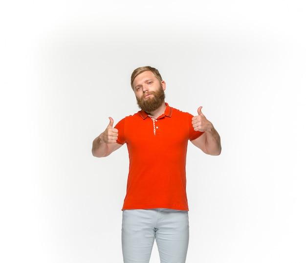 Close-up van jong man lichaam in lege rode t-shirt die op witte ruimte wordt geïsoleerd. bespotten voor ontwerpconcept