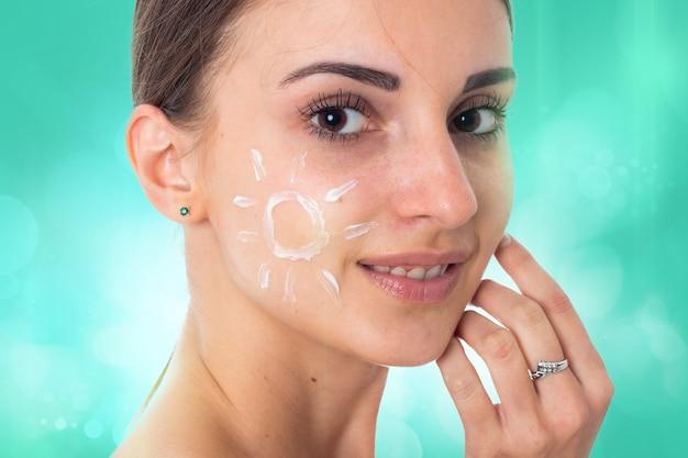 Close up van jong meisje zorgt voor haar huid met crème geïsoleerd op een witte achtergrond. gezondheidszorgconcept. lichaamsverzorgingsconcept. jonge vrouw met een gezonde huid.
