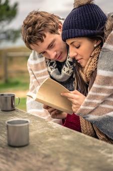 Close-up van jong mooi paar onder deken leesboek in een koude dag met zee en donkere bewolkte hemel op de achtergrond