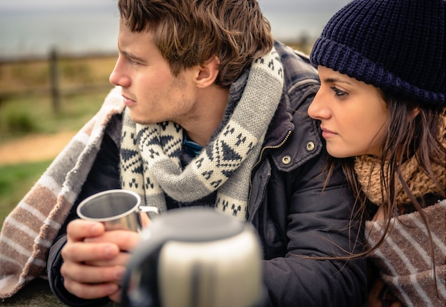 Close-up van jong mooi stel onder deken met warme drank op een koude dag met donkere bewolkte lucht op de achtergrond