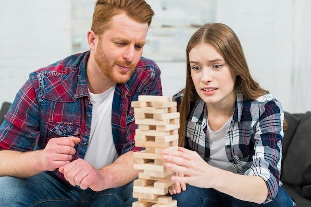Close-up van jong paar die de houten bloktoren spelen