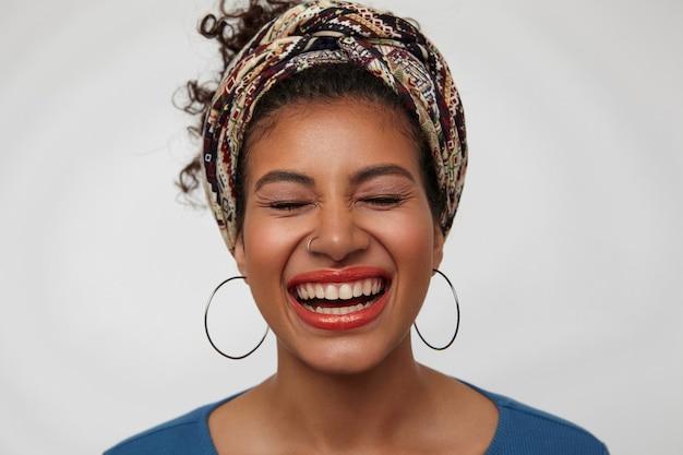 Close-up van jonge aangenaam uitziende brunette donkerhuidige vrouw die haar ogen gesloten houdt terwijl ze vrolijk lacht, staande op een witte achtergrond met gekleurde hoofdband