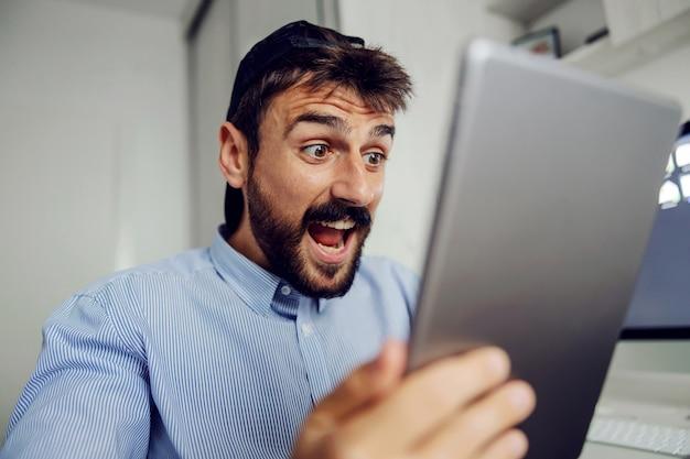 Close-up van jonge aantrekkelijke bebaarde man gekleed business casual kijken naar tablet.