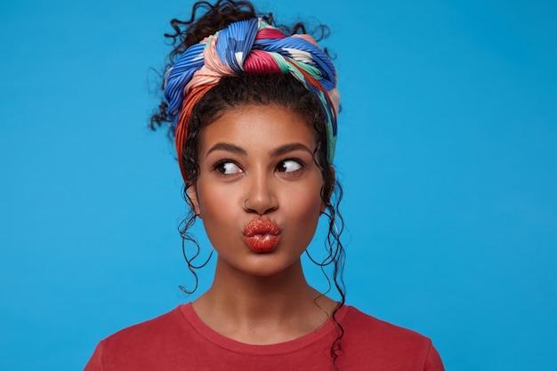 Close-up van jonge aantrekkelijke donkerharige dame met krullen gekleed in gekleurde kleding die opzij kijkt terwijl ze haar lippen pruilt, staande over blauwe muur