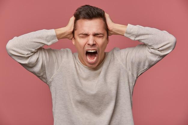Close up van jonge aantrekkelijke man in lege longs leeve, staat op roze achtergrond met gesloten ogen en schreeuwen, kijkt boos en ongelukkig, raakt hoofd.