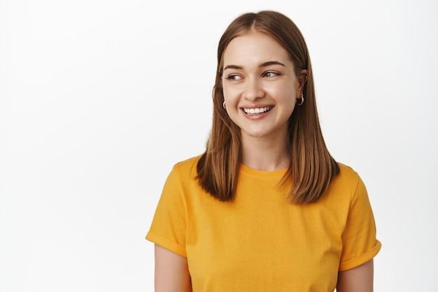 Close-up van jonge aantrekkelijke vrouw met licht kort haar, geel t-shirt dragen, witte tanden glimlachen, links kijkend naar lege ruimte voor verkoop banner, logo plaats, staande over witte muur