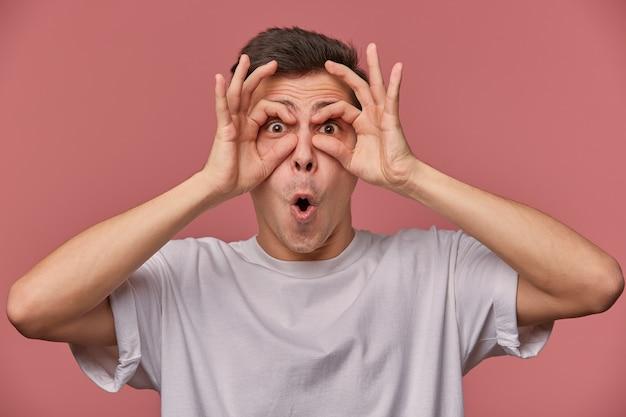 Close-up van jonge afgevraagd man in leeg t-shirt, ziet er dacht oke gebaren, maskers maken met vingers, staat op roze met verbaasde uitdrukking.