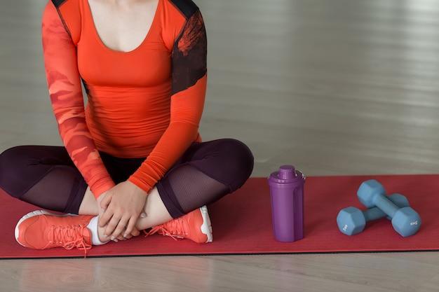 Close-up van jonge atleet in pak zittend op tapijt naast halter en water uit fles in een lege sportschool tijdens training, kopieer ruimte