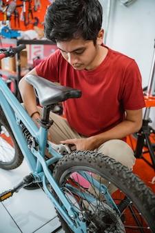 Close up van jonge aziatische monteur die pedalen installeert met een moersleutel