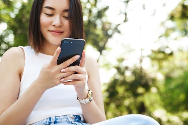 Close-up van jonge aziatische vrouw die mobiele telefoon met behulp van zittend in park