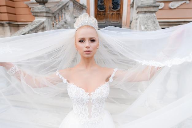 Close-up van jonge bruid houdt haar sluier in haar handen en op straat en ziet er recht uit