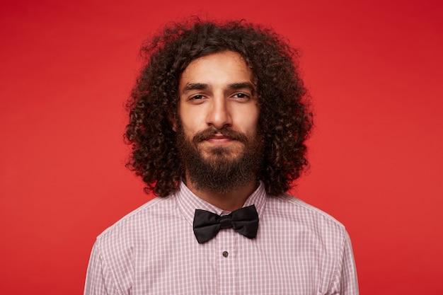 Close-up van jonge charmante donkerharige krullende man met weelderige baard die naar camera kijkt met gevouwen lippen, elegante kleding draagt terwijl hij tegen rode achtergrond staat
