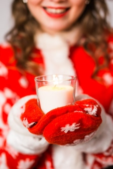 Close-up van jonge charmante vrouw in een santa-pak houdt een kaars