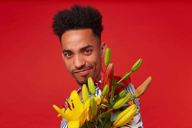 Close-up van jonge coole donkere man, draagt in hawaiiaans shirt, kijkt naar de camera met grappige uitdrukking, houdt gele en rode bloemen, staat op rode achtergrond.