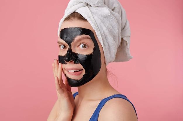 Close up van jonge denkende dame na douche met een handdoek op haar hoofd, met zwart masker, gezicht raakt, staat.