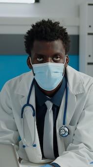 Close up van jonge dokter met gezichtsmasker in medische kast