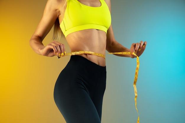 Close up van jonge en sportieve vrouw met fit buik en meter op gradiënt achtergrond perfect lichaam
