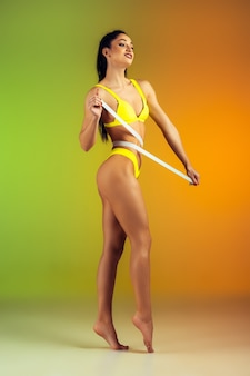 Close-up van jonge fit en sportieve vrouw met meter in stijlvolle gele badmode op kleurovergang muur perfect lichaam klaar voor de zomer
